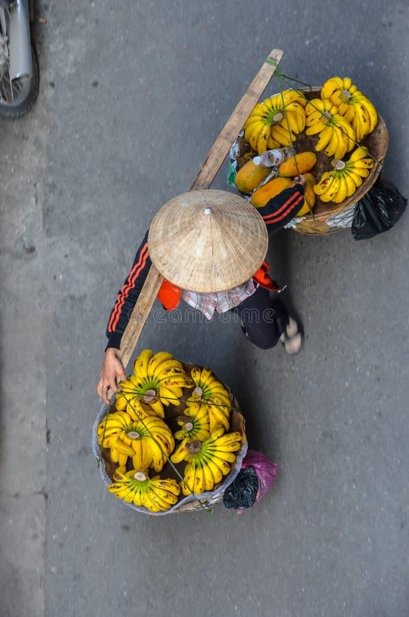 Vietnamese vrouw die bananen vervoeren aan de markt royalty-vrije stock foto's