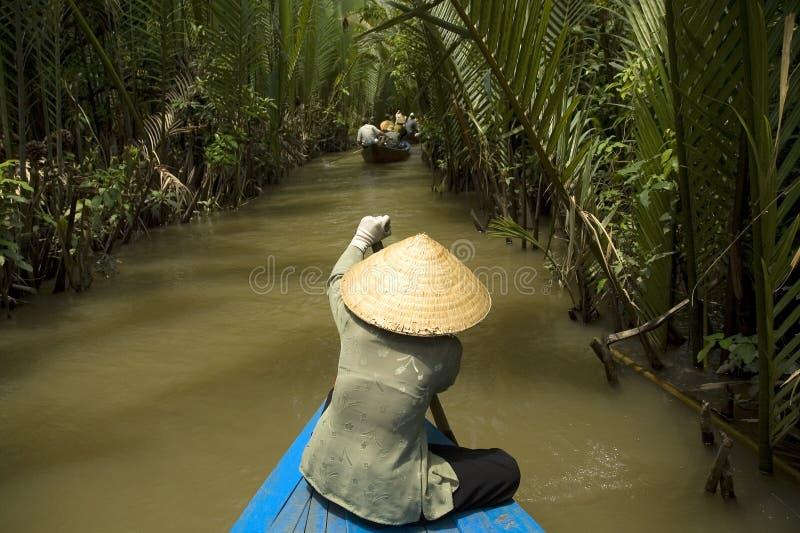 Vietnamese vrouw die een boot roeit stock afbeelding