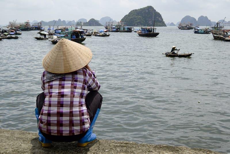 Vietnamese vrouw in het traditionele asinahoed letten op aan Halong-Baai royalty-vrije stock afbeelding