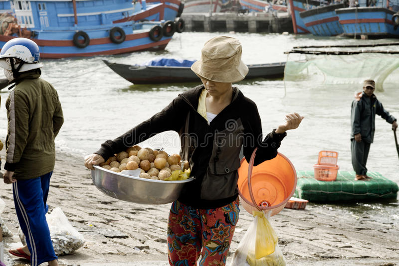 Vietnamese woman carrying a large bowl with deep fried sweet bread royalty free stock photos