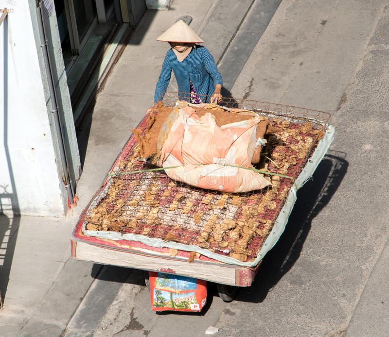 Vietnamese woman pushing a cart with large old mattress stock photo