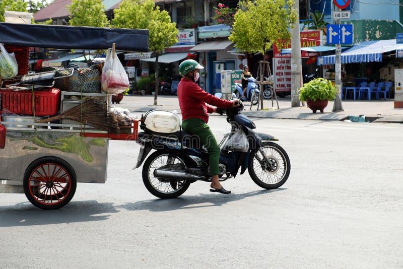 Vietnamese woman ride motorbike pull food cart stop on street royalty free stock images
