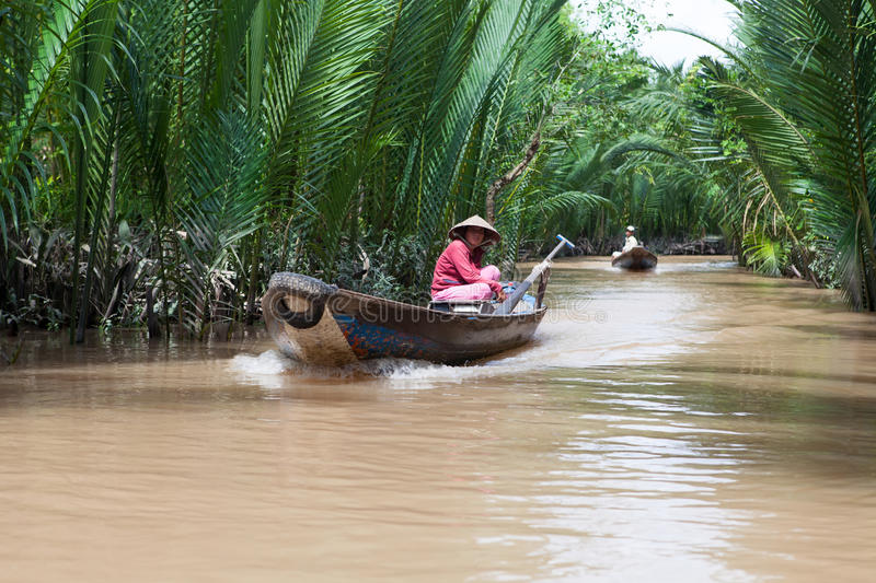 Vietnamese woman rowing a boat in Mekong River royalty free stock photography