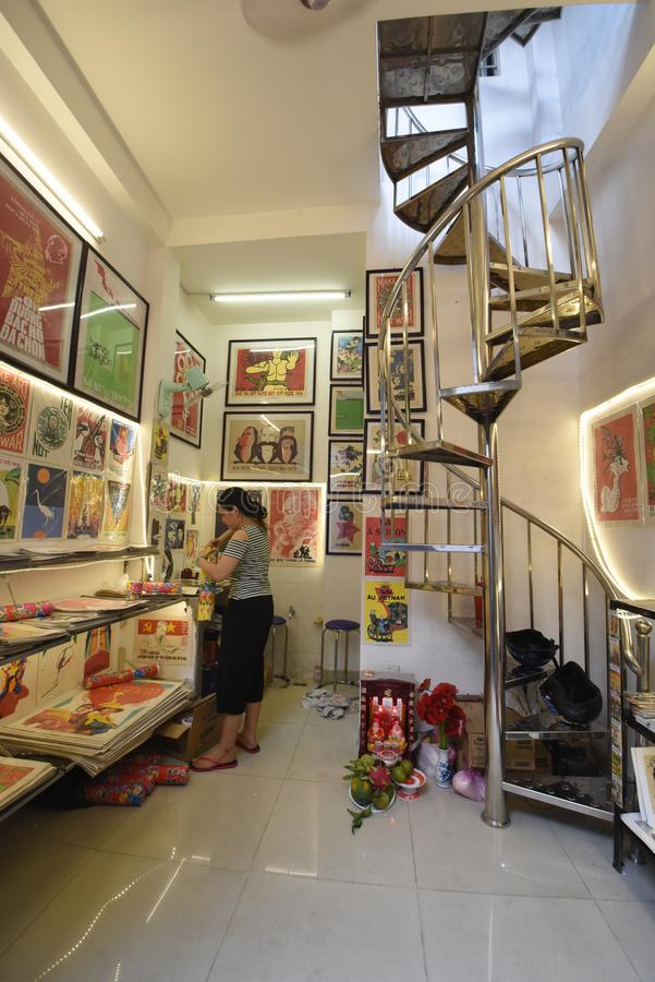 Vietnamese woman seller prepares a protection tube at her propaganda posters shop in Ho Chi Minh City, Vietnam royalty free stock images