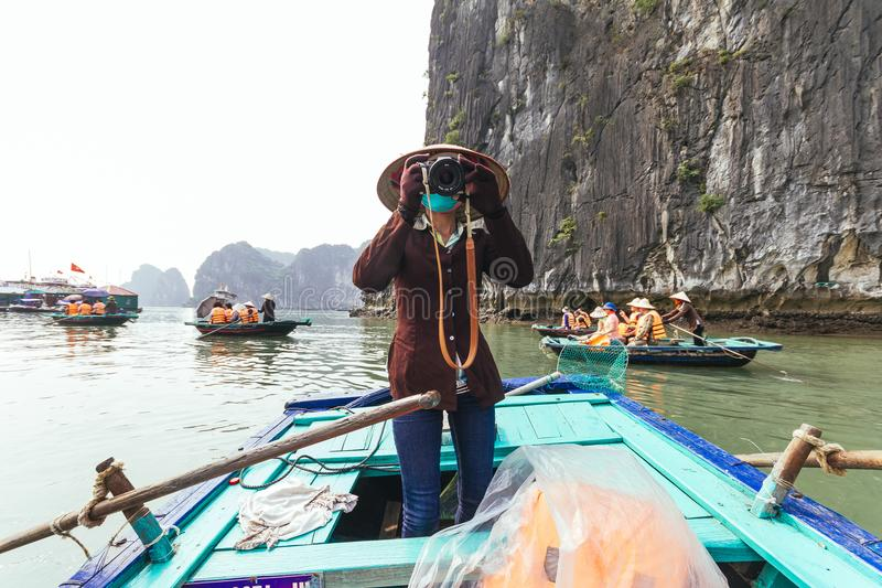 Vietnamese woman take photos on rowing boat with limestone island in background in summer at Halong Bay. Quang Ninh, Vietnam stock photo