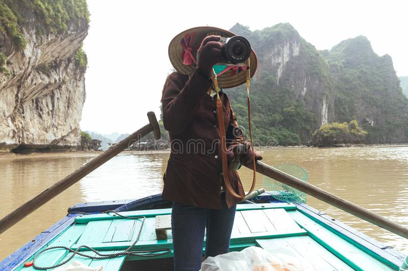 Vietnamese woman take photos on rowing boat with limestone island in background in summer at Halong Bay. Quang Ninh, Vietnam royalty free stock photography