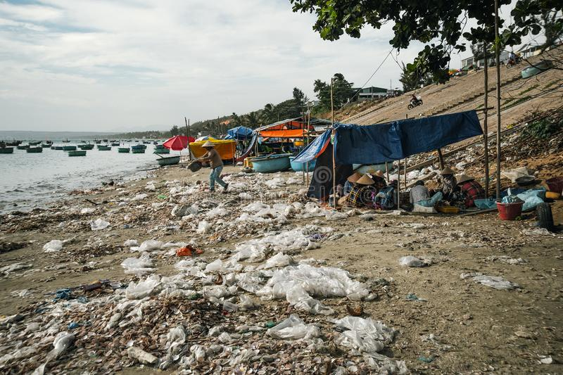 Vietnamese woman throws garbage on the beach by the sea. Dump by the sea. bad ecology in Southeast Asia. Fishermen village in MUI royalty free stock image