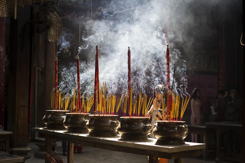 Vietnamese woman in traditional dress ao dai praying with incense stick in the burning pot of the Chinese pagoda in Ho Chi Minh stock images