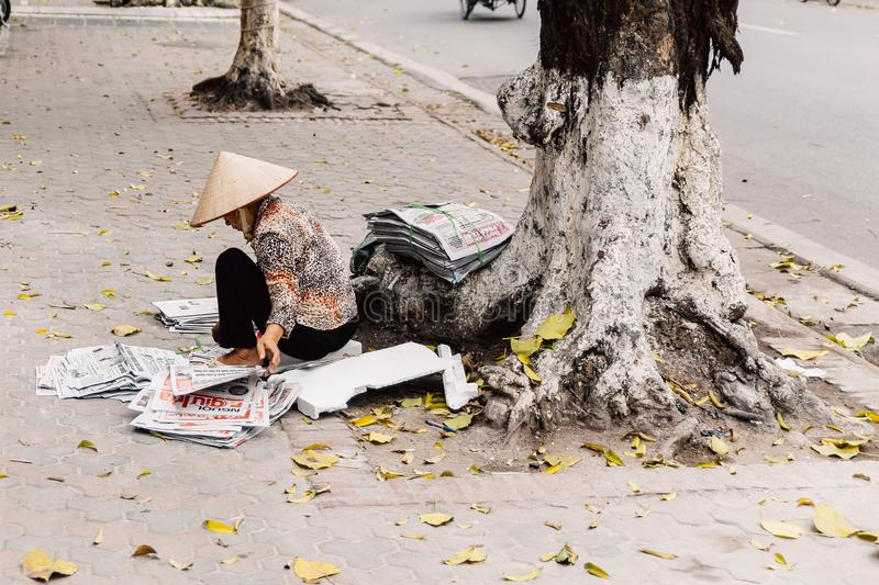 Vietnamese woman wearing asian conical hat sit and prepare newspapers for sell under the tree at Hanoi, Vietnam royalty free stock photos