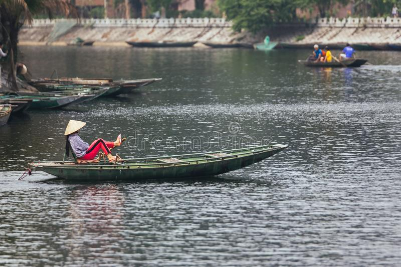 Vietnamese woman wearing purple long arm t-shirt conical hat rowing boat by her feet on the river at Trang An Grottoes. royalty free stock photo