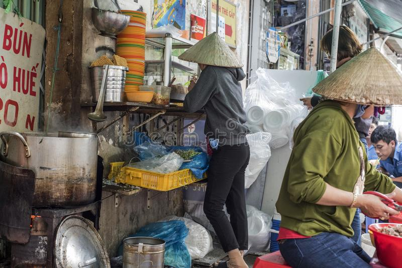 Vietnamese women prepare food at a street soup shop in Ho Chi Minh City, Vietnam stock photography