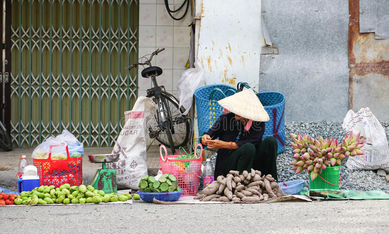 Vietnamese women selling many tropical fruits. Ben Tre, Vietnam - Jun 25, 2015. Vietnamese women with the conical hat selling many tropical fruits at the market royalty free stock photo