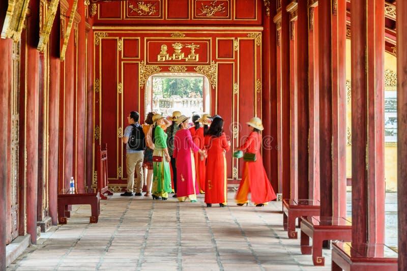 Vietnamese women in traditional garments Ao dai. Hue. Hue, Vietnam - April 4, 2018: Vietnamese women in colorful traditional garments Ao dai walking along red stock photo