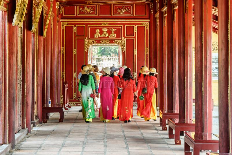 Vietnamese women in traditional garments Ao dai, Hue. Hue, Vietnam - April 4, 2018: Vietnamese women in traditional garments Ao dai walking along red wooden stock photo