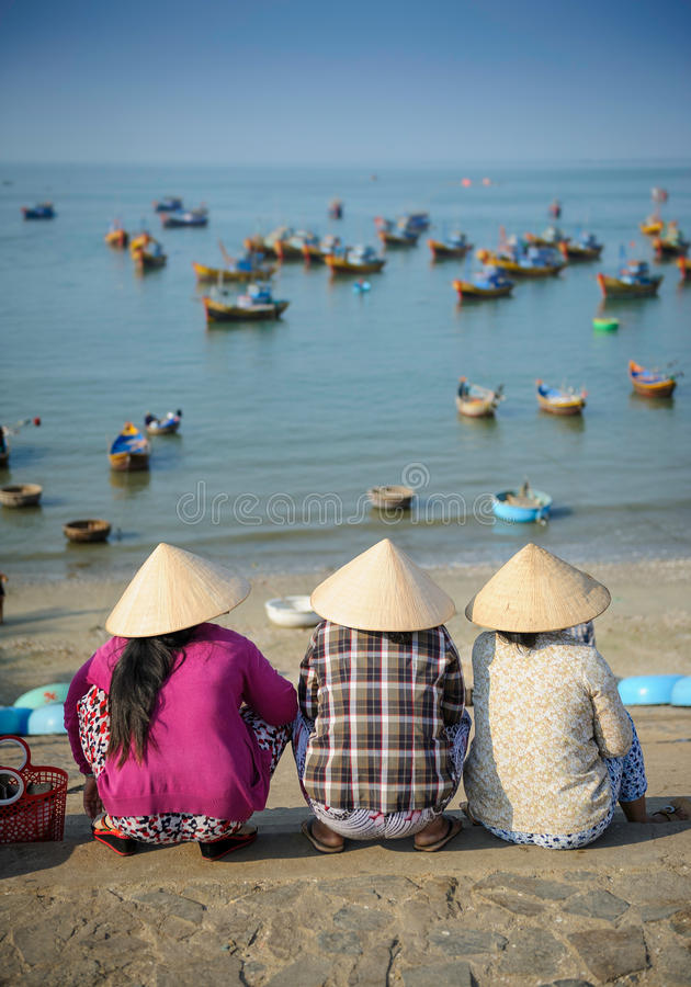 Vietnamese women waiting for fishing boats royalty free stock photos