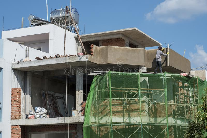 Vietnamese worker smooths concrete wall on top a condo being built in Ho Chi Minh City, Vietnam royalty free stock photography