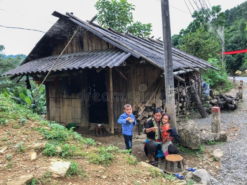 Vietnamesische Dame mit zwei Jungen, die Reis vor ihrem Haus essen lizenzfreies stockfoto