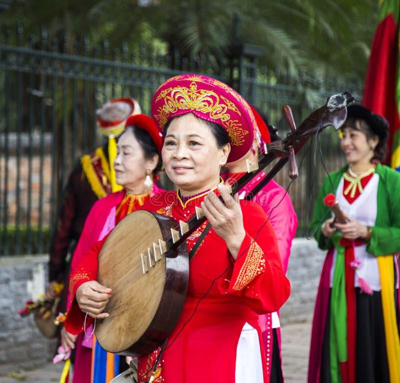 Vietnamesische Frau im Trachtenkleid und in Hut, die Tranh-Instrument spielen stockfotografie