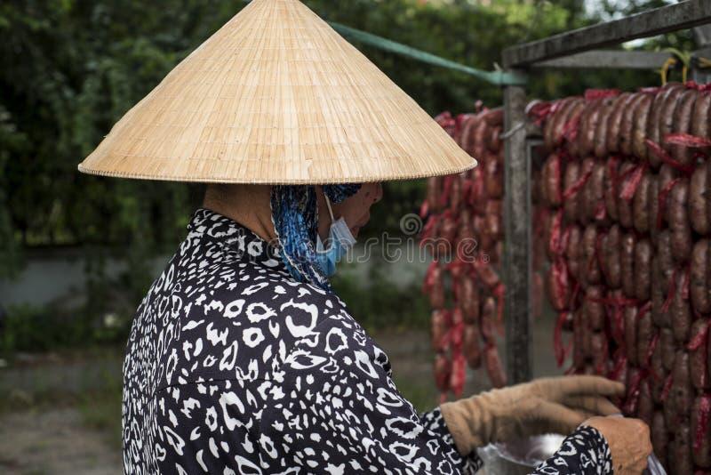 Vietnamesische Frau verkauft Würste durch die Straße in Süd-Vietnam lizenzfreie stockfotografie