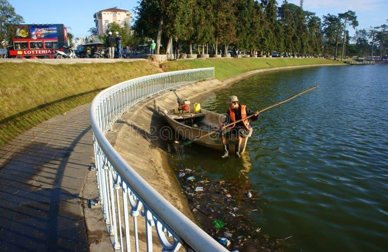 Vietnamesische Hygienearbeitskraft heben Abfall vom See auf lizenzfreie stockfotos