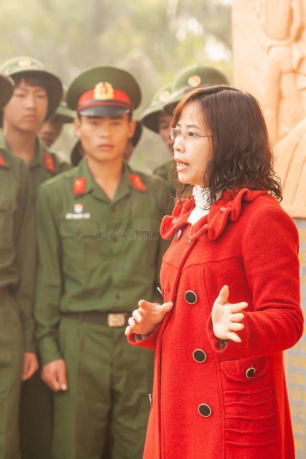 Vietnamesische Professorfrau, die zum jungen vietnamesischen Soldaten an der Statue des französischen allgemeinen Des Castries ko lizenzfreie stockfotografie