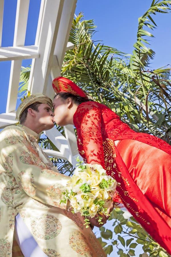 Vietnamesischer amerikanischer Hochzeitspaarkuß stockbilder
