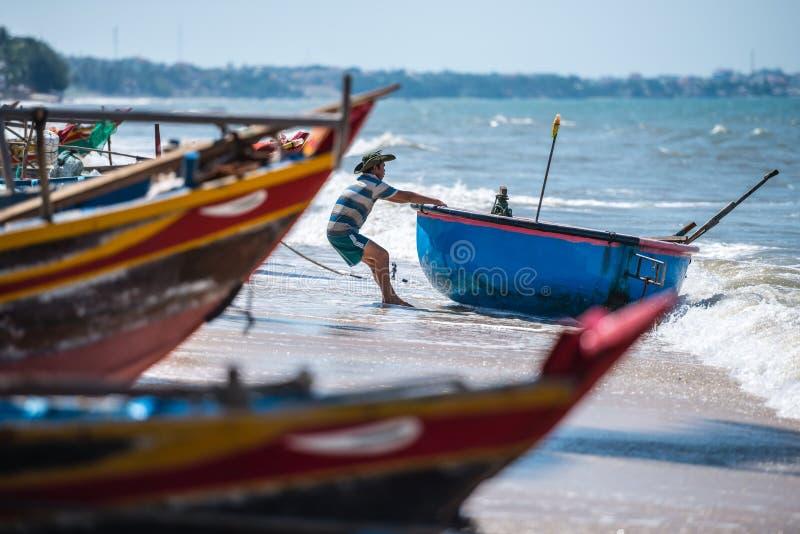 Vietnamesischer Fischer ziehen seinen Fischen Coracle zum Meer während seiner Abschaltzeit am Fischer heraus lizenzfreie stockbilder