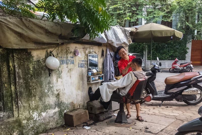 Vietnamesischer Friseur schneidet einen Kunden im Straßenfriseursalon stockfoto