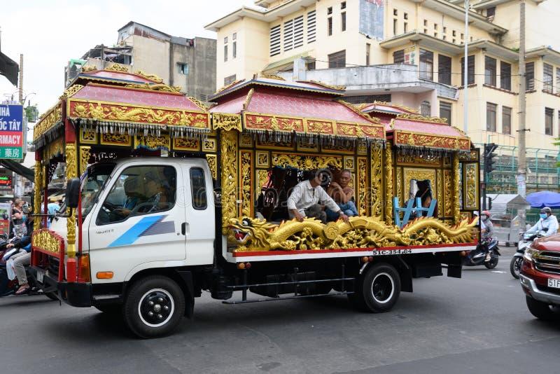 Vietnamesischer Leichenwagen mit goldenen Dekorationen und Drache in den Straßen von Ho Chi Minh City lizenzfreie stockbilder