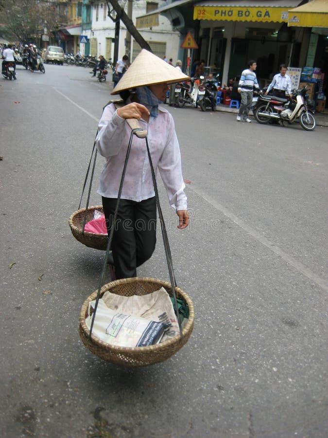 Vietnamesischer Verkäuferassistent, der entlang die Straßen suchen den Käufer geht stockfotografie