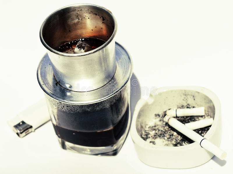 Vietnamesisk cofe och cigarett med askfatet som isoleras på vita clo royaltyfria foton