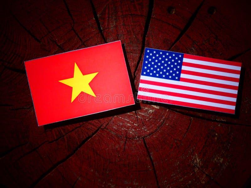 Vietnamesisk flagga med USA flaggan på en trädstubbe arkivfoto