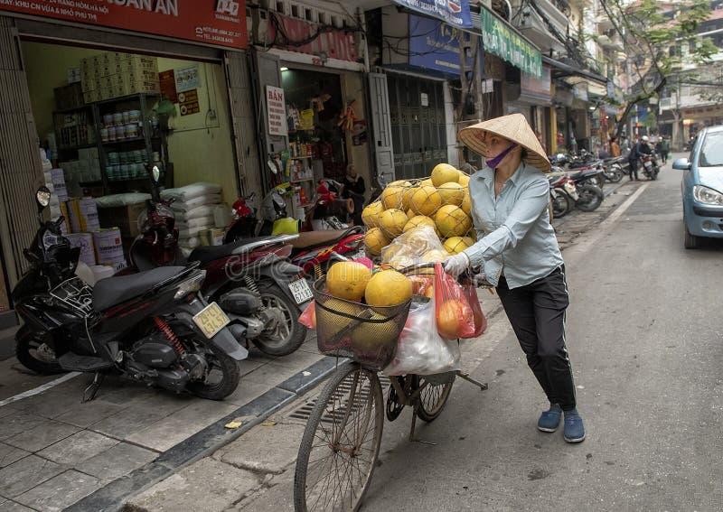 Vietnamesisk gatuförsäljare i Hanoi, på till salu bärande gods för cykel arkivbilder