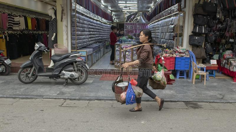Vietnamesisk gatuförsäljare i Hanoi som promenerar en gata som bär två korgar av mat som rymms av en bamburam över hennes skuldra royaltyfria foton