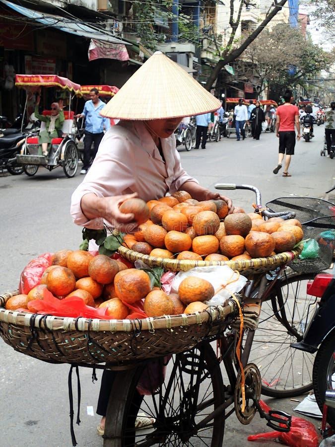 Vietnamesisk gatuförsäljare med frukt - Hanoi - Vietnam royaltyfria bilder
