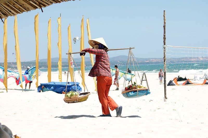 Vietnamesisk kvinna som säljer frukter på den Mui Ne stranden arkivfoto