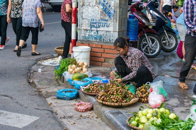 Vietnamesisk kvinna som säljer tropiska frukter på kerben på gata M royaltyfria foton