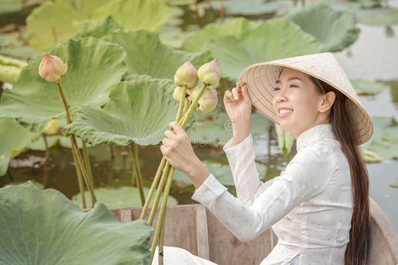 Vietnamesisk kvinnlig p? ett tr?fartyg som samlar lotusblommablommor Asiatiska kvinnor som mot efterkrav sitter p? tr?lotusblomma royaltyfri fotografi