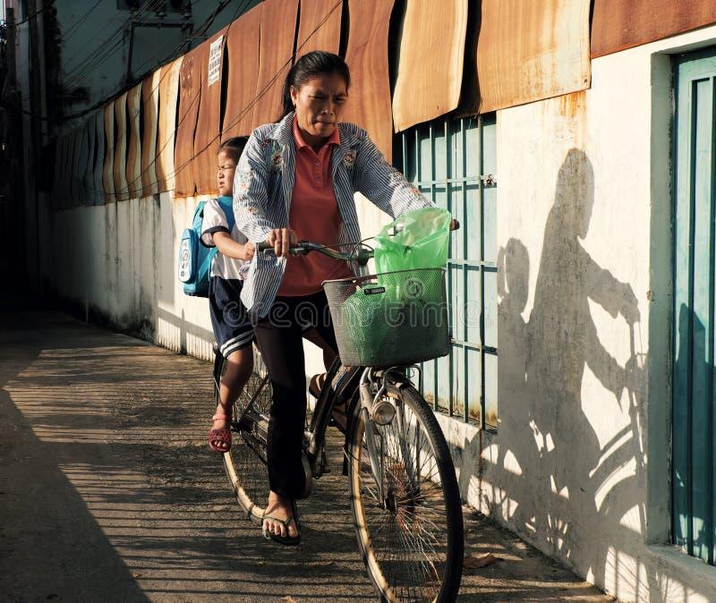 Vietnamesisk modertransportdotter att gå att skola med cykeln i varm solskendag royaltyfria bilder