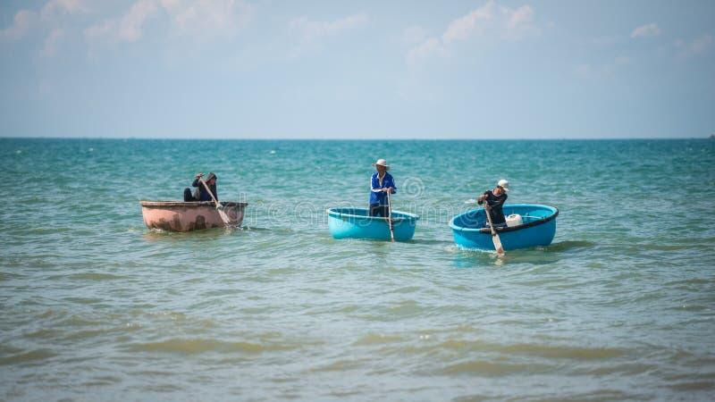 Vietnamesiska fiskare drar på deras fiskecoracles till havet för att fiska på fiskaren Village, Mui Ne, Vietnam royaltyfria bilder