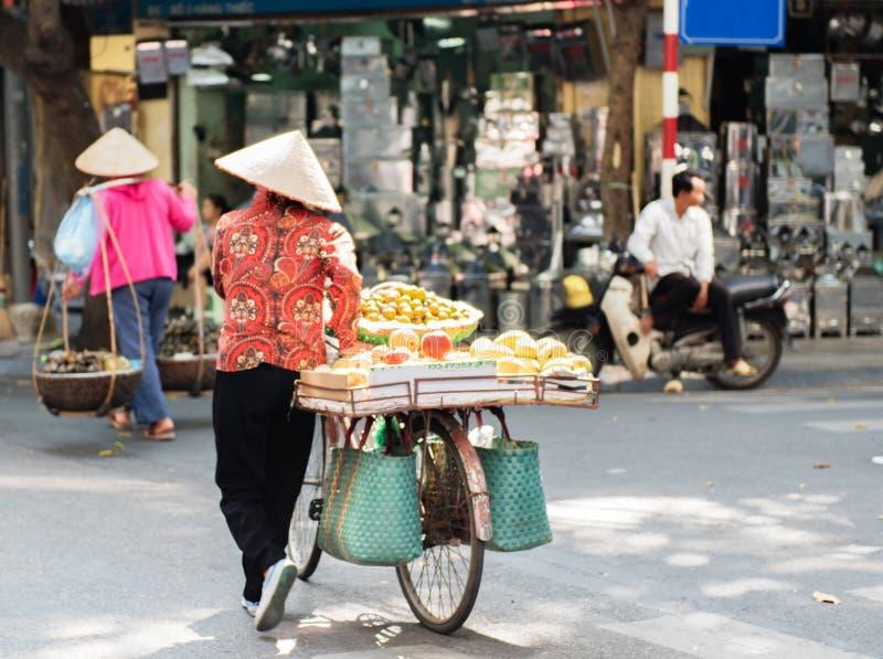 Vietnamesiska gatuförsäljare agerar och säljer deras grönsaker och fruktprodukter i Hanoi, Vietnam royaltyfri foto