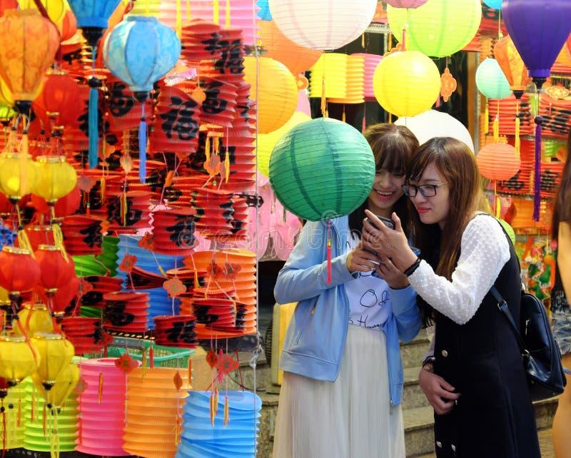 Vietnamesiska härliga unga flickor har rolig tid med vänner på nattlyktagatan royaltyfri bild