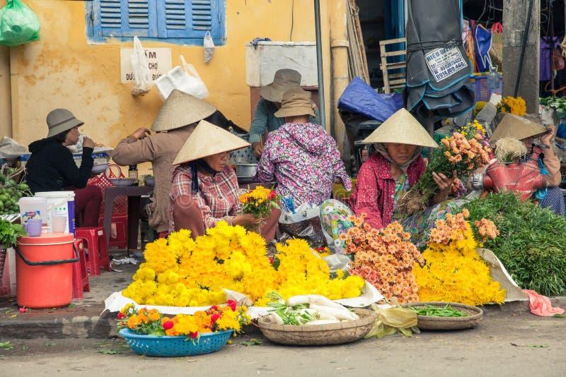 Vietnamesiska kvinnor i den koniska hatten som säljer blommor på gatamarken royaltyfri bild