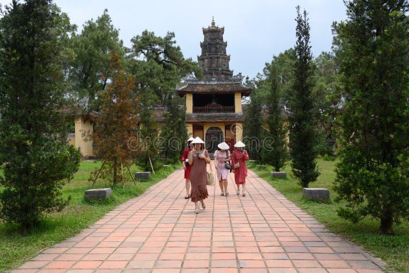 Vietnamesiska kvinnor rullar i trädgården Thien Mu Pagoda, Hue City, Vietnam royaltyfri bild