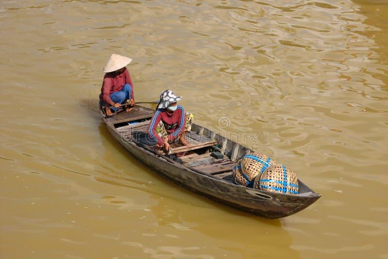 Vietnamesiska kvinnor som paddlar på deras lilla fartyg royaltyfri bild