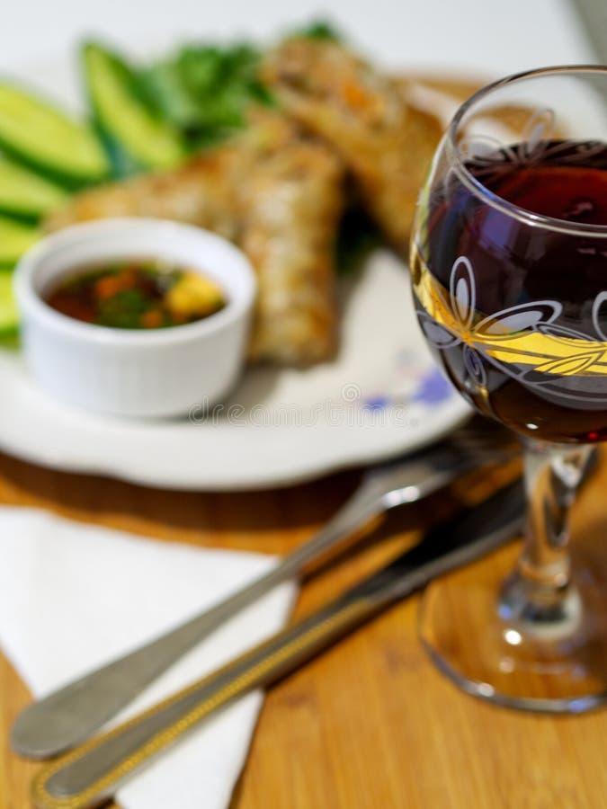 Vietnamesiska nems eller stekte vårrullar på en platta, med grönsaker och sås arkivfoton