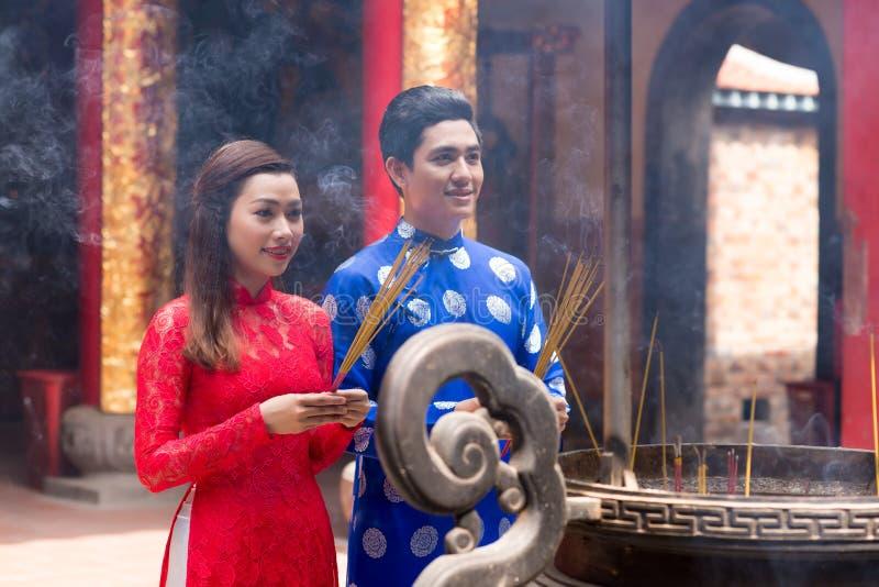 Vietnamesiska par med rökelsepinnar arkivbilder
