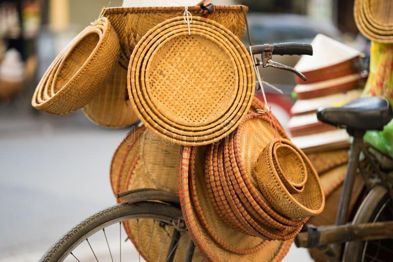 Vietnamesiska traditionella bambukorgar på försäljare cyklar i den Hanoi gatan royaltyfri bild