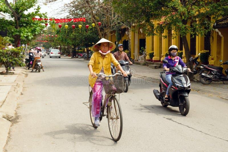Vietnamesiskt folk på en cykel och mopeder på en väg i mitten av staden med gula hus och röda och gula garneringar royaltyfri fotografi