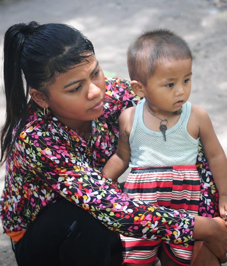 Vietnamesiskt minoritetbarn som kramar hans moder royaltyfria bilder